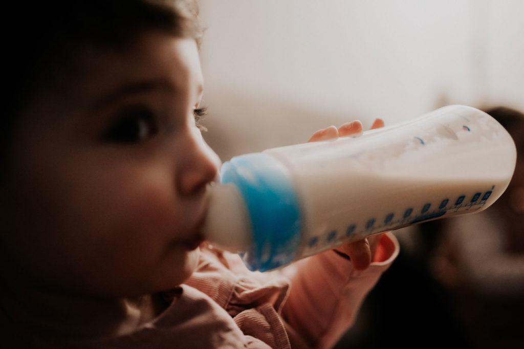 photo d une petite fille qui prend son biberon