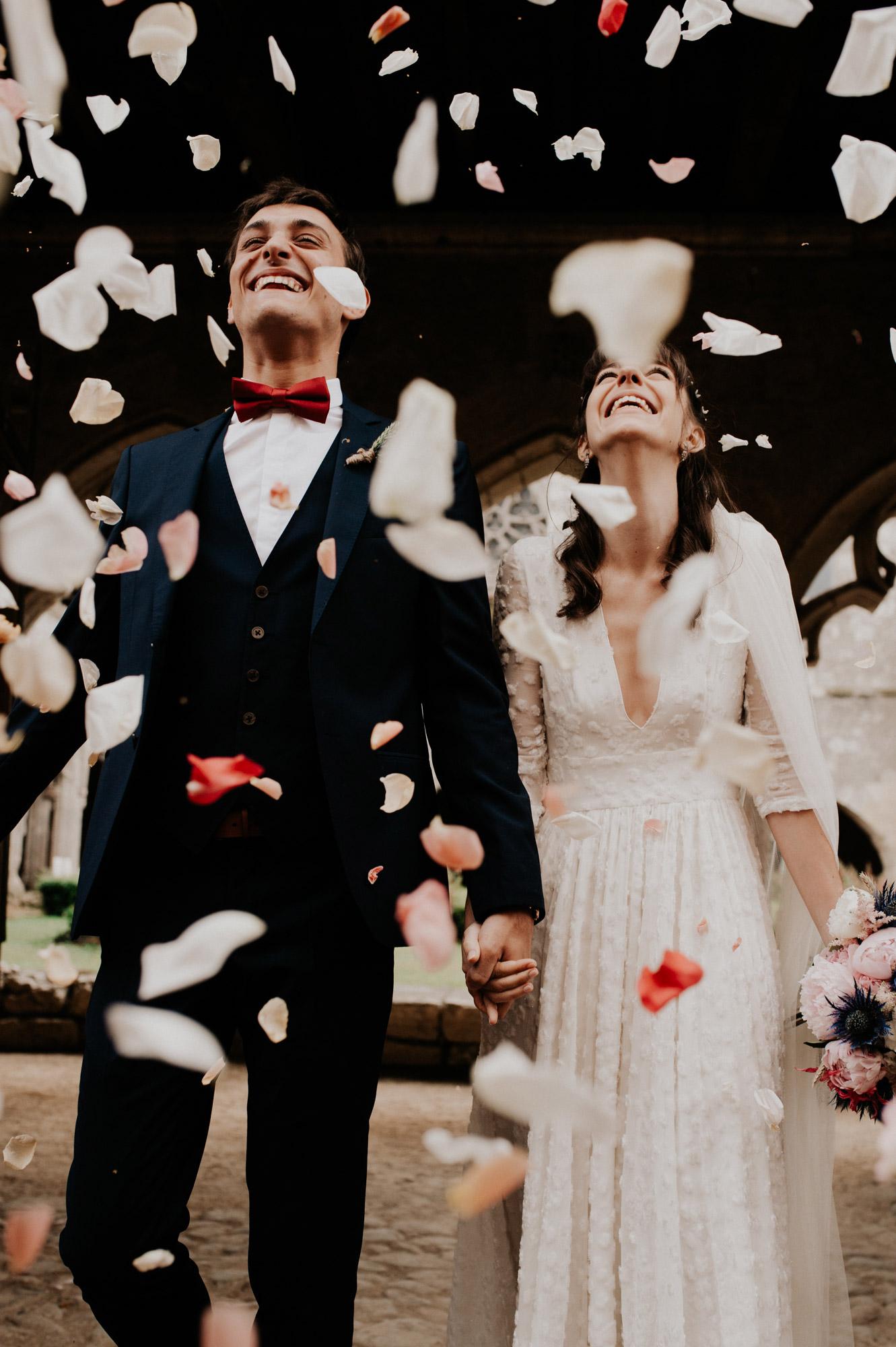 les maries sortent de la collegiale de la romieu sous les fleurs et sont rayonnants de bonheur